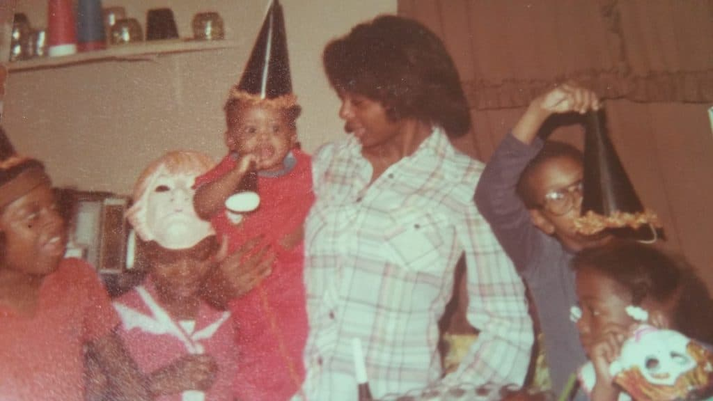 This is Deborah Pretty (P.Y.) holding her 1 year old son during at his first Birthday Party.
