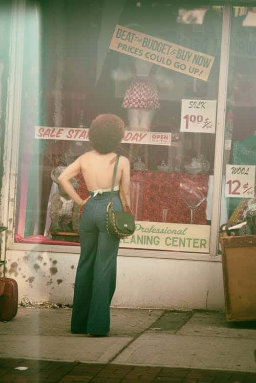 lady in front of store looking at sale price,