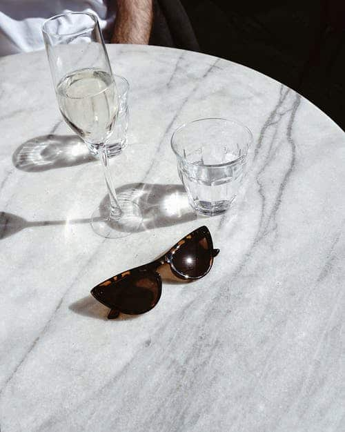 photo of table with wine glasses and sunglasses