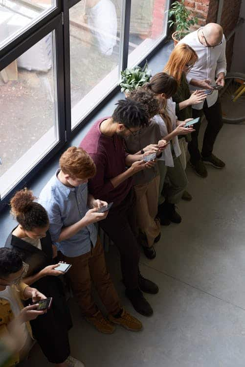 a line of people texting all standing along a wall near a window