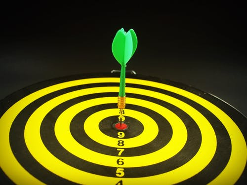 yellow and black tart board with an arrow directly in the center of the bulls-eye. Demonstrating target marketing